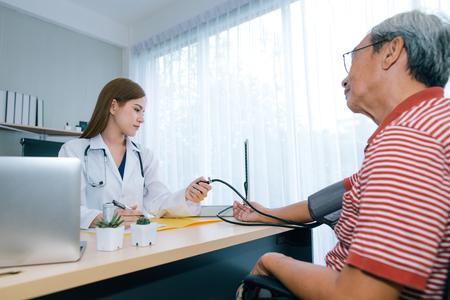 Photo pour Female doctor checking blood pressure ff senior man patient - image libre de droit