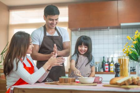 Foto de Daughter and parent preparing the bake  Family concept. - Imagen libre de derechos