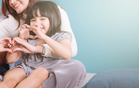 Foto de little girl making heart shape sit in mom lap. - Imagen libre de derechos