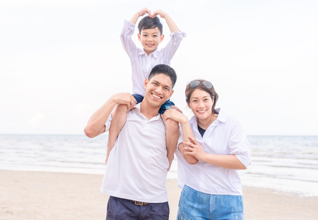 Foto de portrait happy family outdoors on a beach smiling - Imagen libre de derechos