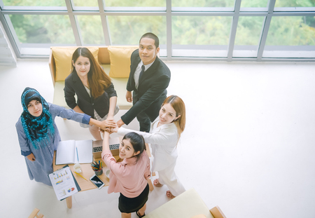 Foto de Top view of Business people in team stack hands together as unity and teamwork in office. young Asian businessman and group togetherness collaboration - Imagen libre de derechos