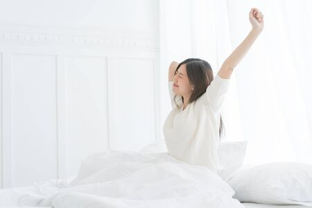 Foto de Young Asian woman in the morning she stretching in her bed in the bedroom - Imagen libre de derechos