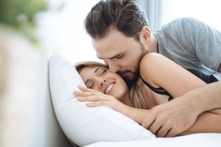 Photo for Young couple kissing cheek in the bed wake up in the morning. loving couple in bedroom - Royalty Free Image