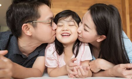 Photo for Asian Parents kissing their little daughter on both cheeks. family portrait. - Royalty Free Image