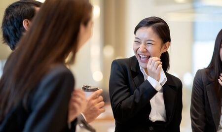 Photo pour Asian business people talking and laughing in office building. Young businessman and businesswoman colleague talk to each other during the break. - image libre de droit