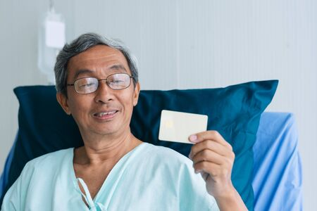 Photo pour Asian patient elderly man showing credit card on hospital bed in hospital. payment health Insurance medical treatment concept - image libre de droit