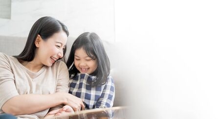 Photo pour Mother and her daughter child girl playing her mom in sofa living room at home. Happy Asian family concept - image libre de droit