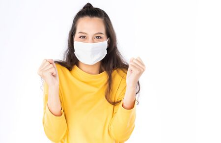 Photo pour Young happy Asian woman wearing hygienic mask to prevent infection corona virus Air pollution pm2.5 she wearing a yellow sweater shoot in shot isolated on white background - image libre de droit