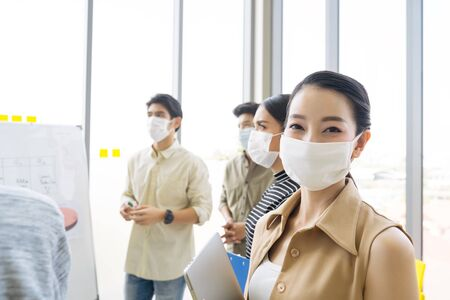 Photo pour Group of asian business people meeting and working in office and wear mask for protect  prevent infection corona virus covid 19. - image libre de droit