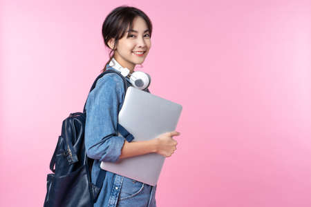 Photo pour Portrait of smiling young Asian college student with laptop and backpack isolated over pink background - image libre de droit