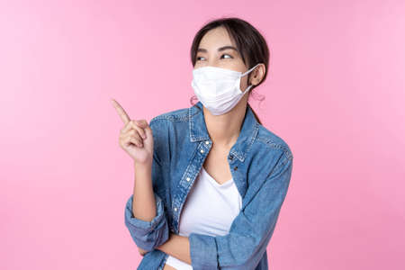 Photo pour Young happy Asian woman pointing finger hands up to copy space wearing hygienic mask - image libre de droit