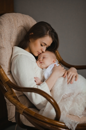 Photo for young mother holding her newborn baby sitting in armchair - Royalty Free Image