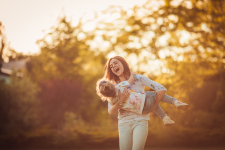 Photo pour Mother and little daughter playing together in a park - image libre de droit