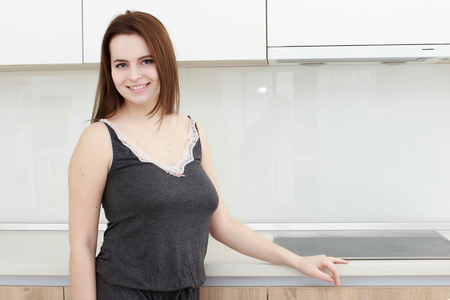 Serious attitude. Young smiling lady standing in a kitchen.