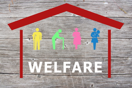 Welfare concept on wooden background with colored home and old man, disabled, pregnant and woman with baby