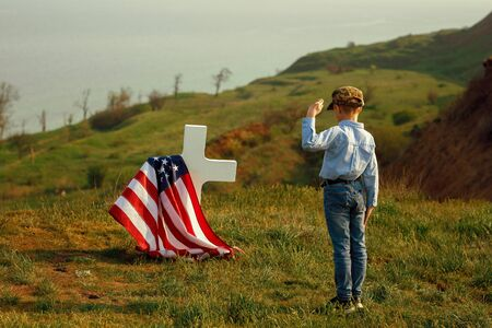 Foto per a young boy in a military cap salutes his father's grave on memorial day - Immagine Royalty Free