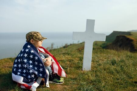 Foto per a young boy in a military cap, covered by the flag of the united states sitting on the grave of his deceased father. May 27th memorial day - Immagine Royalty Free