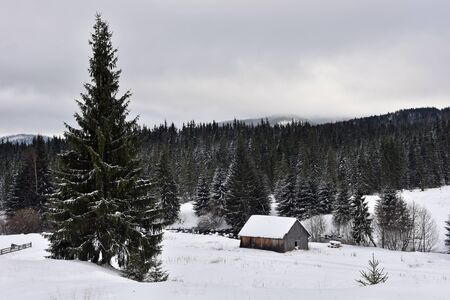 Winter landscape with a small wooden lodge in the mountains