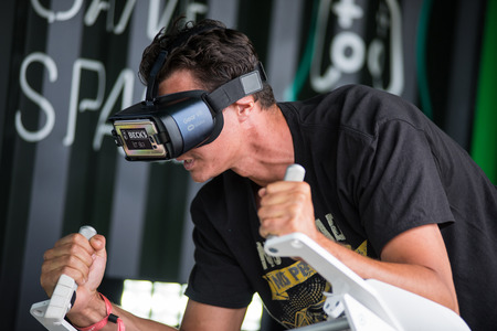 BONTIDA, ROMANIA - JULY 14, 2017: A guy using Samsung virtual reality headset. Man playing with a VR oculus googles at Electric Castle festival tech zone