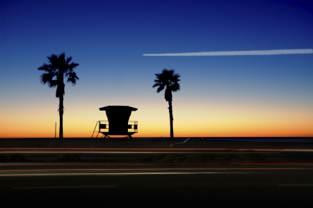 Lifeguard Tower with Palm trees at sunset. Airplane flying across the orange, blue sky and cars in motion.