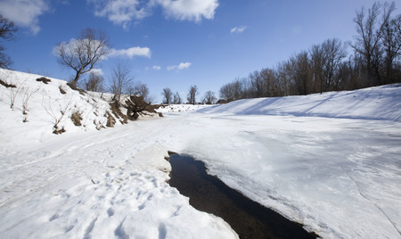 marvelous landscape in early spring on the river and white clouds on blue sky on a sunny day