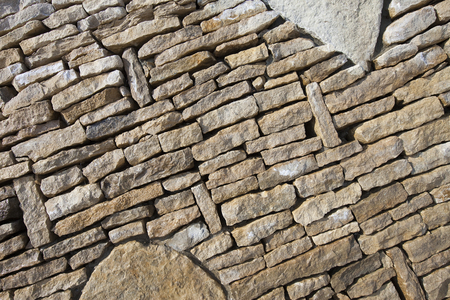 close-up part of the wall of natural stone lined pattern in sunlight