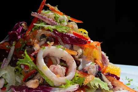 close-up of exquisite seafood salad with fresh herbs and vegetables on a white plate