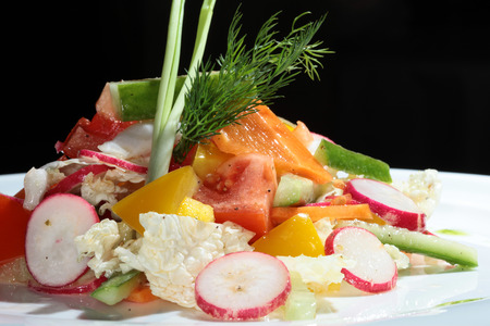 macro beautiful vegetarian salad from vegetables on a white plate studio