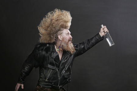 Closeup portrait adult biker in black leather jackets and high mohawk and beard with a bottle