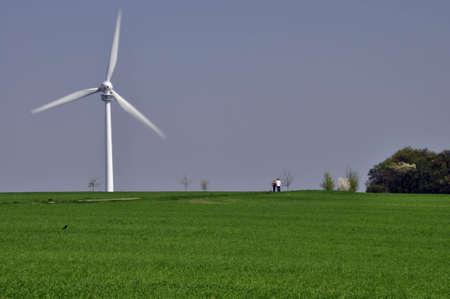 Windrad als alternative Energiequelle mit blauem Himmel und grÃŒnem Gras Wind as an alternative energy source with a blue sky and green grass