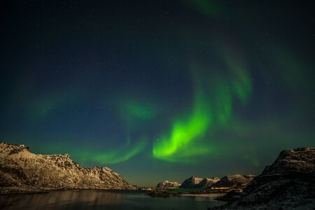 Photo pour Dramatic northern lights, Aurora borealis over fjord mountains with many stars on the sky in Lofoten islands, Norway, long shutter speed. - image libre de droit