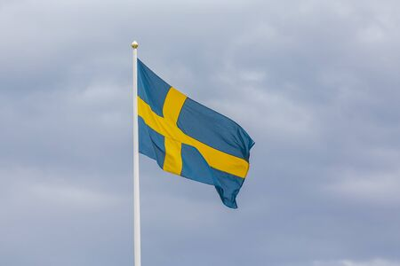 Swedish flag as proudly fluttering in the wind against a blue sky.