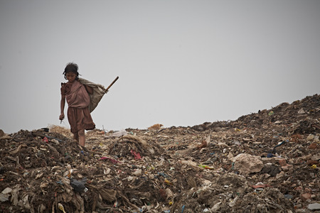 Photo for New Delhi, India, July 2009.Girl in a garbage dump outside the city. - Royalty Free Image
