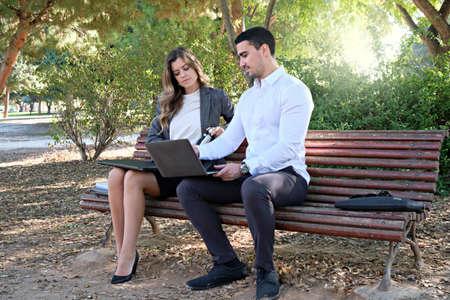 Photo pour Young businesswoman negotiating with executive man on park bench - image libre de droit