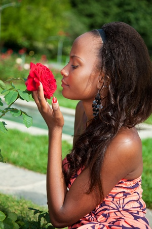Outdoor portrait of a young beautiful african american girl smelling flowers