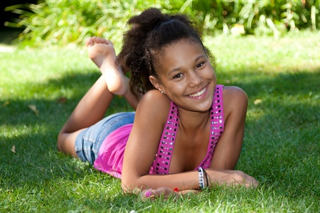 Young african american teenage girl  lying on the grassの写真素材