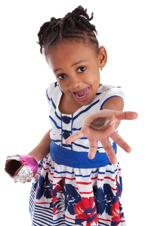 Photo pour Little african american girl eating chocolate easter egg, isolated on white background - image libre de droit