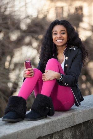 Outdoor of a  portrait happy young african american teenage girl listening to musicの写真素材