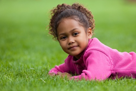 Outdoor portrait  of a cute little African Asian girl lying down on the grass
