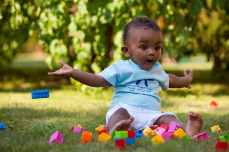 Portrait of a little african american baby boy playing outdoor in the grass