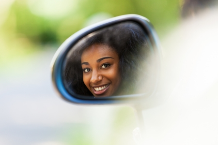Young black teenage driver seated in her new convertible car - African people
