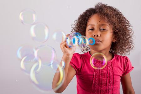 Cute little African American girl blowing soap bubbles