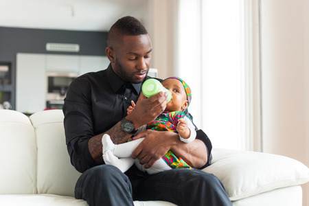 Young african american father giving milk to  her baby girl in a baby bottle