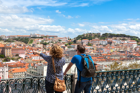 Tourist watching to Lisbon rooftop from Sao Pedro de Alcantara viewpoint - Miradouro in Portugal