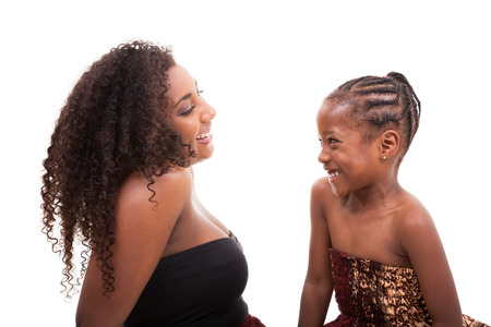 African american mother with her daughter looking and smiling at each other, isolated on white backgroundの写真素材