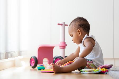 Foto de Portrait of little African American little girl sitting on the floor and playing  - Black people - Imagen libre de derechos