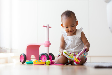 Portrait of little African American little girl sitting on the floor and playing  - Black people