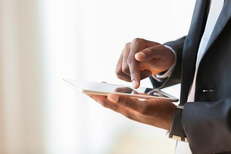 Foto de African american business man using a tactile tablet over white background - Black people - Imagen libre de derechos