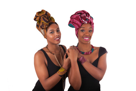 Photo pour Young beautiful african womans wearing a traditional headscarf - image libre de droit