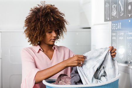 Photo pour Young black African American woman holding a basket of clothes to be washed in a automatic laundry - image libre de droit